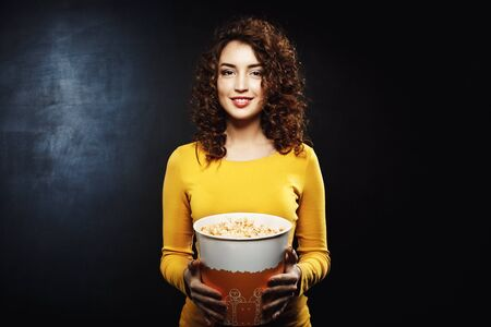 feature film: Portrait of curly woman holding popcorn bucket looking straight Stock Photo