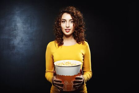 flick: Charming young woman with popcorn bucket isolated on black background Stock Photo