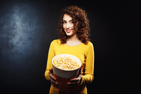 treating: Portrait of attractive woman treating to popcorn with cheerful smile Stock Photo
