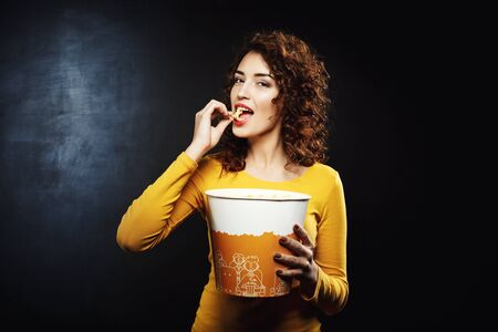 cheesy: Attractive woman eating cheesy popcorn looking pleased and happy Stock Photo