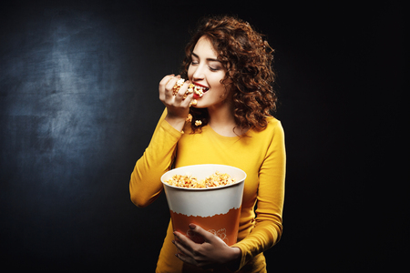 Hungry woman eats handful of popcorn while waiting for movie