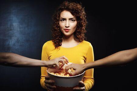 Displeased woman holding popcorn bucket in hands looking straight