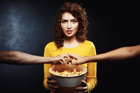 delightful: Grumpy woman holding popcorn bucket and doesnt want to share Stock Photo