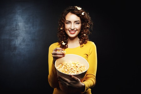 funny girl with popcorn on hair smiling and looking straight stock