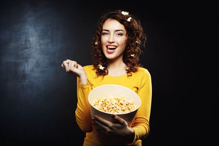 feature film: Attractive girl eating tasty salty sweet popcorn watching tv shows Stock Photo