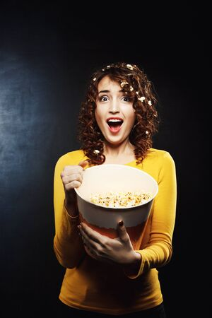 feature film: Emotional woman watching horror movie and looks scared sreaming loudly