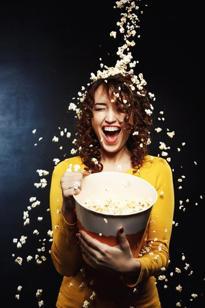 cheesy: Laughing young woman staying under cheesy popcorn shower at cinema