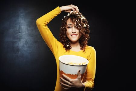Funny girl eating popcorn while watching shows at home party