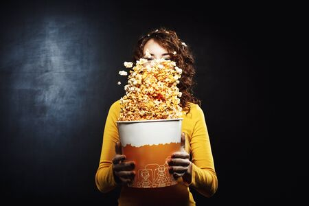 Pretty girl having fun at movie theatre shaking popcorn bucket Stock Photo