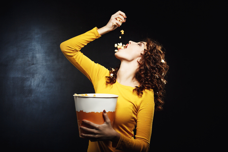 Attractive young woman pouring popcorn in mouth holding big bucket Stock Photo