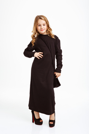 Girl in black maxi dress posing with hand on hip.