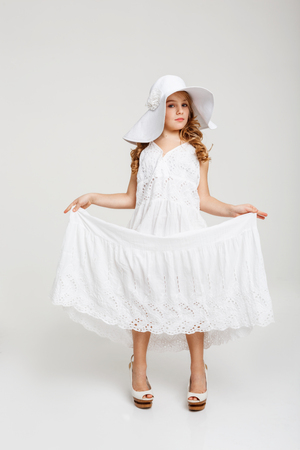womanlike: Nice girl with big curls holds skirt out, looking staight. Stock Photo