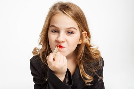 womanlike: Closeup of funny blonde girl puttng on red lipstick. Stock Photo