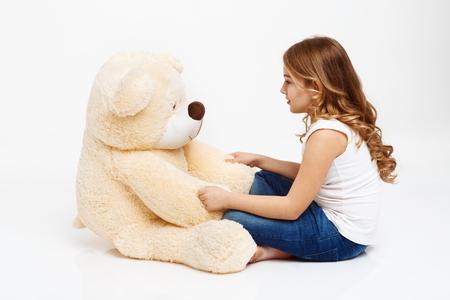 Girl talking to toy bear as it is a friend.