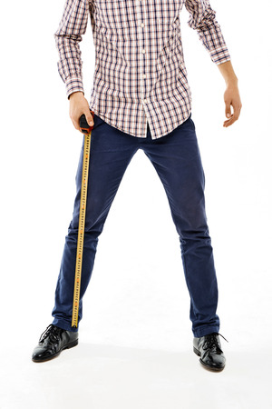 Close-up confident young man with tape measure wearing casual plaid shirt and blue jeans. Straddle. Isolated Stock Photo