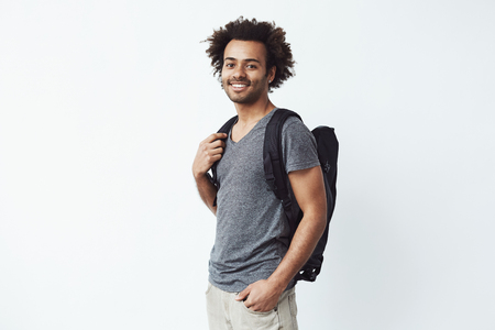 strive for: Portrait of cheerful african man with backpack smiling looking at camera ready to go on a long hiking trip or strive for education. White background. Travel or study concept.
