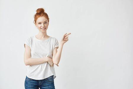 Pretty redhead girl with freckles smiling pointing finger right on white background. Фото со стока