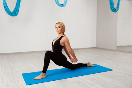 Young beautiful blonde girl practicing yoga in gym.