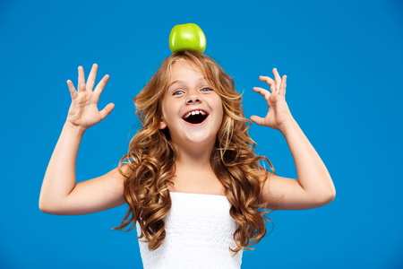Young pretty girl holding apple  on head over blue background. Stock Photo