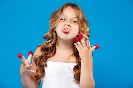Young pretty girl eating raspberry over blue background.