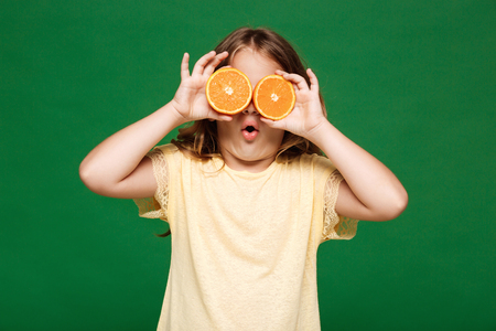 Young pretty girl hiding eyes with oranges over green background. Stock Photo