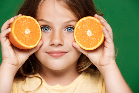 Young pretty girl holding orange over green background. Stock Photo