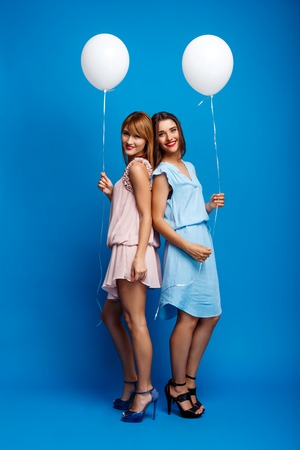 Portrait of two girls resting at party over blue background.