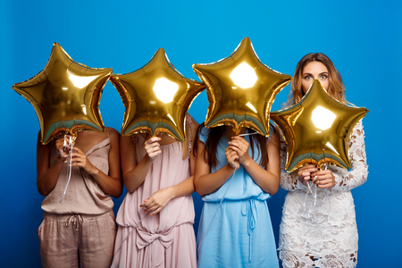 Four beautiful girls resting at party over blue background. Stock Photo