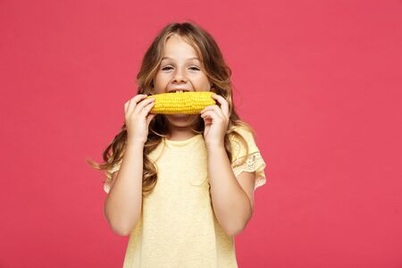 Young pretty girl eating corn over pink background. Stock Photo