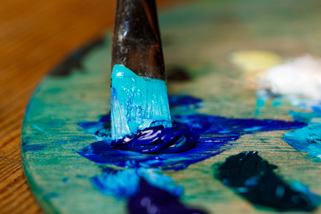Close up photo of mixing oil paints on palette.