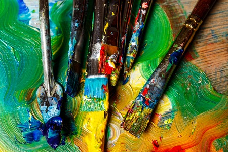 originative: Close up of oil paints and brushes on palette. Above. Stock Photo