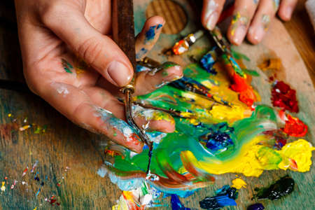 originative: Close up photo of girl mixing oil paints on palette.