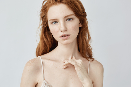 Young beautiful redhead girl with freckles looking at camera. Imagens