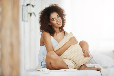 Beautiful african girl in sleepwear smiling looking at camera holding pillow sitting on bed at home. Stock Photo