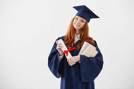 Beautiful redhead female graduate smiling holding books and diploma over white background.