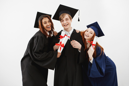 Happy friends graduates smiling holding diplomas looking at camera over white background.