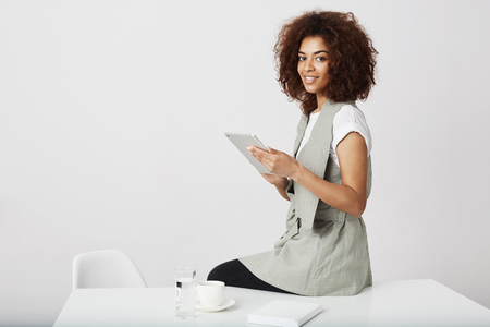Beautiful african girl smiling holding tablet sitting at workplace. Copy space.