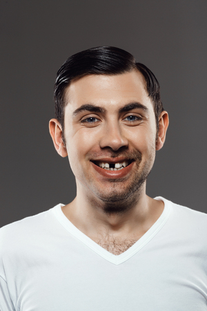 Portrait of young man without tooth over grey background.