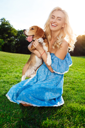 Young beautiful blonde girl walking, playing with beagle dog in park.