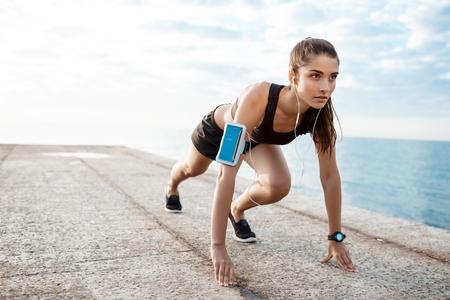 Jonge mooie sportieve meid voorbereiding om over de kust te rennen.