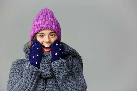 Young beautiful surprised fair-haired girl in knited hat sweater and mittens smiling looking at camera over grey background.