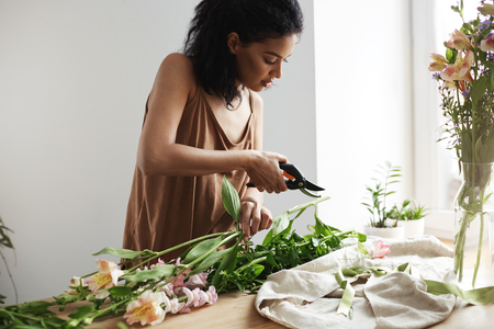 Attractive african female florist cutting flower stems at workplace. White wall background.