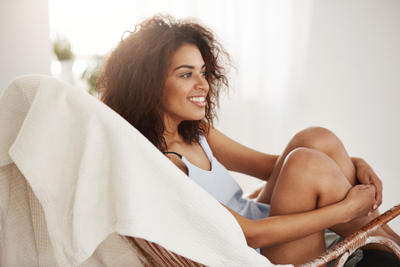 Tender beautiful african girl in sleepwear smiling sitting in chair resting relaxing at home.
