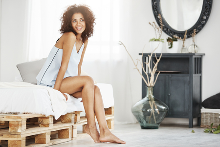 Dreamy tender african girl in sleepwear sitting on bed in morning smiling thinking.