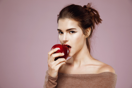 Pretty young girl biting red apple looking at camera over pink background.