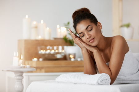 Tender african girl smiling resting relaxing with closed eyes in spa salon. Stock Photo - 78924897