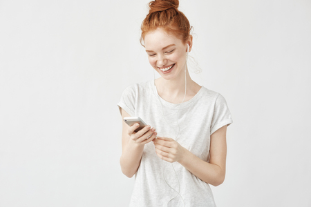Portrait of pretty redhead girl smiling messaging and listening to streaming music in wired headphones over white wall.