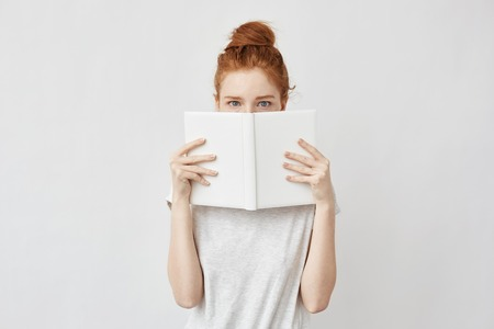Redhead girl hiding face behind notebook looking at camera frightenedly.
