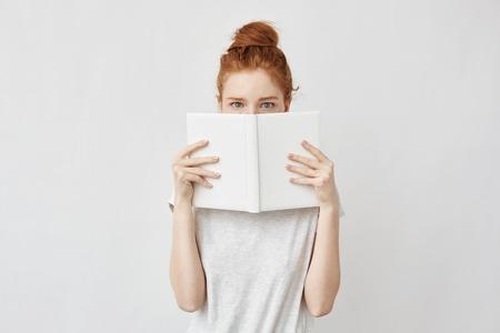 Redhead meisje verbergen gezicht achter notitieboekje kijkend naar de camera bang.