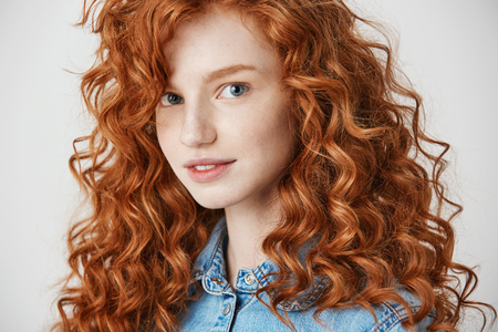 Portrait of pretty redhead girl smiling looking at camera over white background.